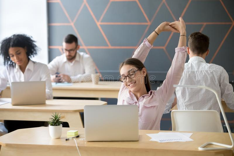 Millennial employee stretching taking break from computer work f. Millennial employee taking break from computer, young businesswoman or student stretching at stock photos