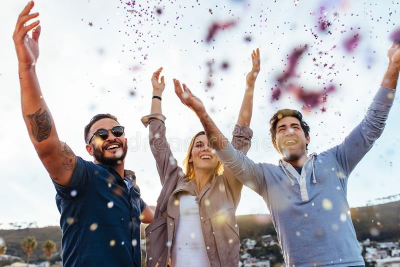 Millennial enjoying at party with confetti. Group of millennial hanging out together on rooftop party. Young men and women friends enjoying at party with stock images