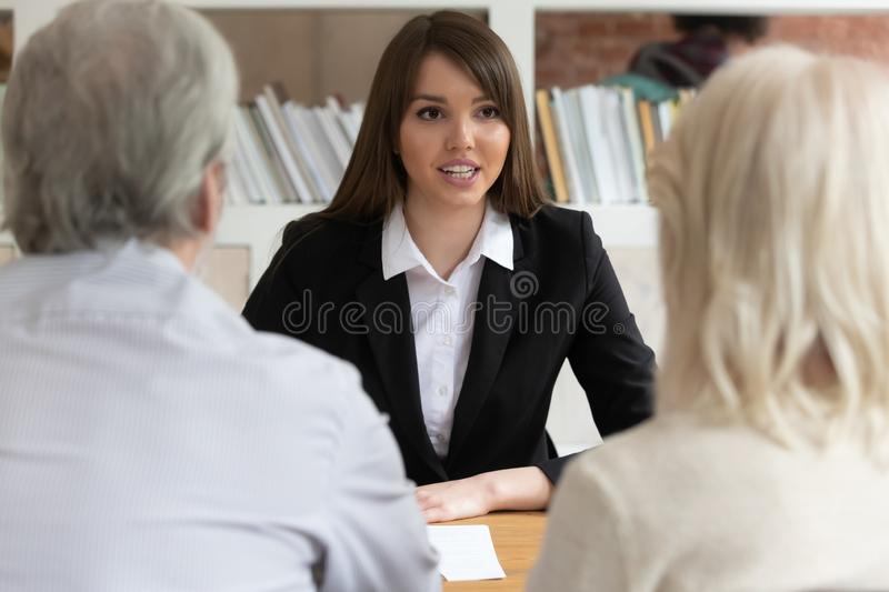 Female bank specialist speak consulting mature clients. Millennial female bank specialist talk meeting with mature clients or customers help with loan or royalty free stock photos