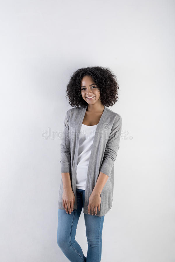 Millennial female model with afro hairstyle. Looking at the camera, indoors stock photography