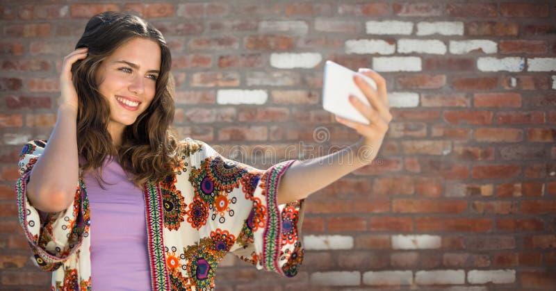 Millennial flicka som tar selfie mot väggen för röd tegelsten royaltyfri fotografi