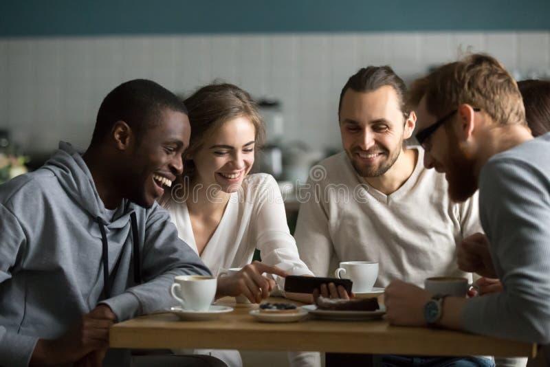Millennial flicka som visar den roliga mobila videoen till vänner i kafé royaltyfri foto