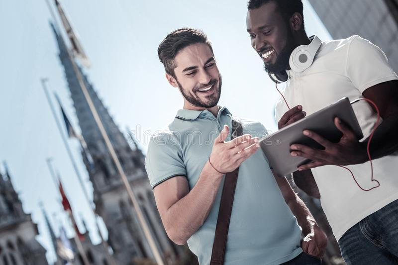 Millennial friends smiling while looking at touchpad stock images