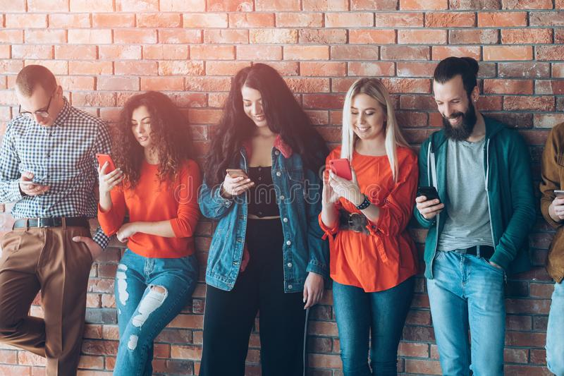 Millennial generation leisure modern smartphones. Millennial generation leisure. Diverse stylish young people leaned against wall, reading fun content on modern royalty free stock photo