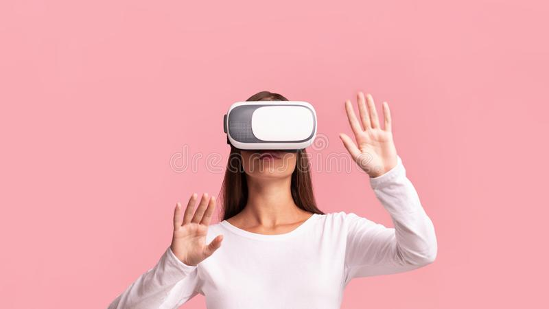 Millennial Girl Using Virtual Reality Headset Over Pink Background, Panorama. VR Concept. Millennial Girl Using Virtual Reality Headset Playing Videogame Over stock images