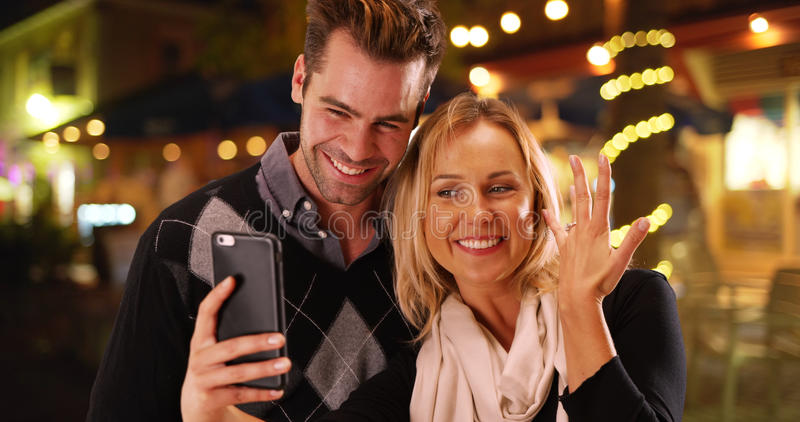 Millennial girlfriend taking selfies with her new engagement ring.  stock photo