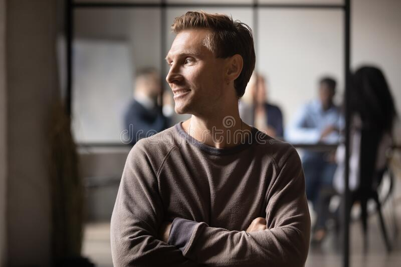 Millennial guy posing in office dreaming about career growth stock photo