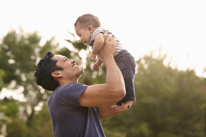 Millennial Hispanic father holding his little baby in the air in the park, close up stock images