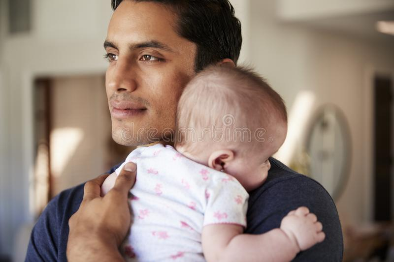 Millennial Hispanic father holding his newborn son close to his chest, head and shoulders, close up royalty free stock photo