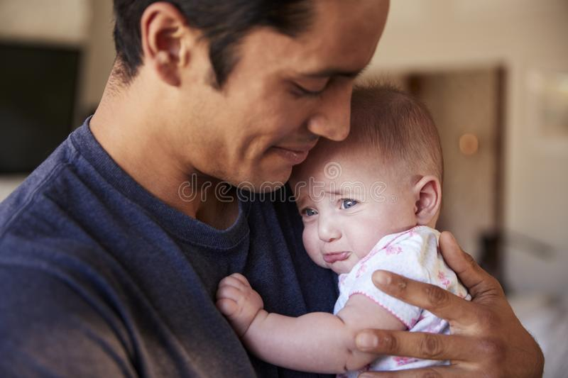 Millennial Hispanic father holding his newborn son, side view, head and shoulders, close up stock image