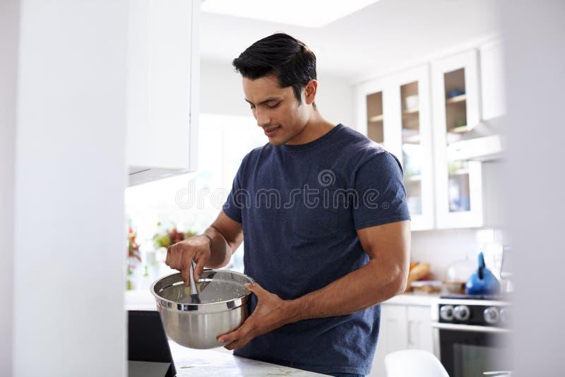 Millennial Hispanic man preparing cake mixture, following a recipe on a tablet computer, close up royalty free stock photos