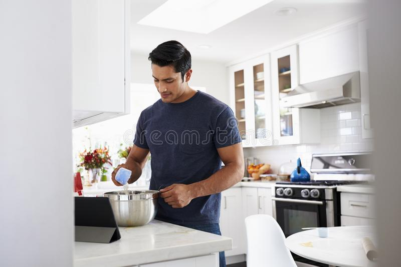 Millennial Hispanic man preparing cake mixture in kitchen, following a recipe on a tablet computer stock images