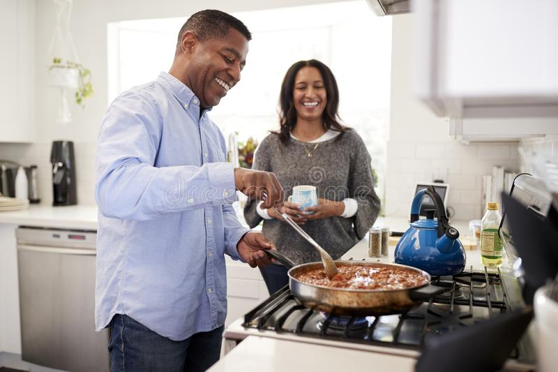 Millennial African American  man standing in the kitchen cooking with his partner standing beside him, backlit stock photo