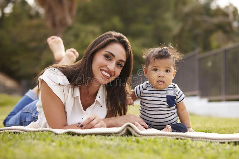 Millennial Hispanic mother lying on a blanket in the park with her baby, smiling to camera stock images