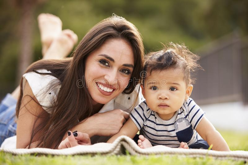 Millennial Hispanic mother lying on a blanket in the park with her baby, smiling to camera, close up stock photo
