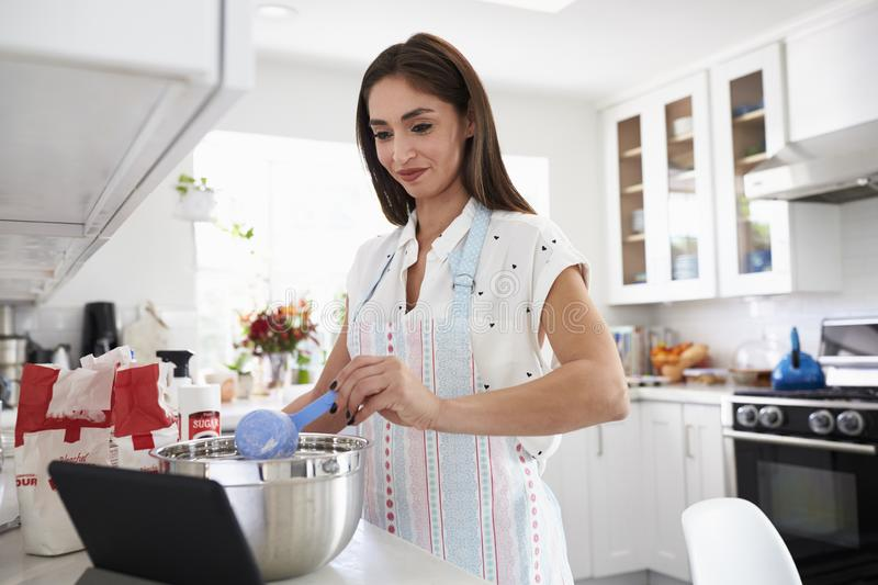 Millennial Hispanic woman adding flour to a cake mixture, following a recipe on her tablet computer royalty free stock images