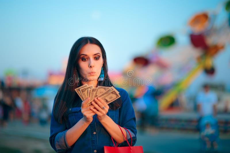 Woman Holding Cash Money at Summer Funfair. Millennial holding banknotes after lucky win in amusement park games stock photos