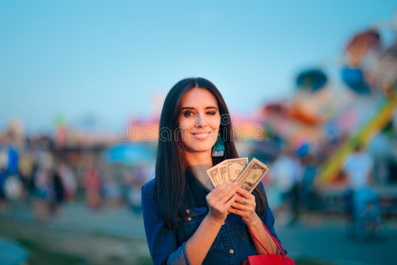 Woman Holding Cash Money at Summer Funfair. Millennial holding banknotes after lucky win in amusement park games stock images