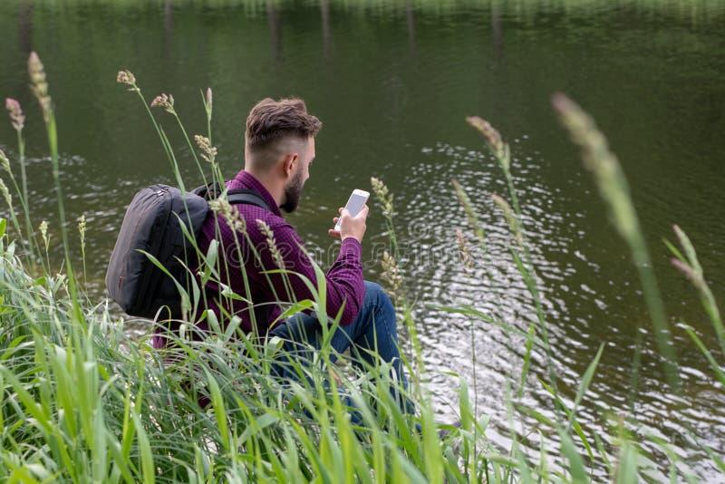 Millennial, jonge kerelzitting op het strand, rivierbank onderzoekt de telefoon, neemt een foto Surfend Internet in telefoon stock foto's