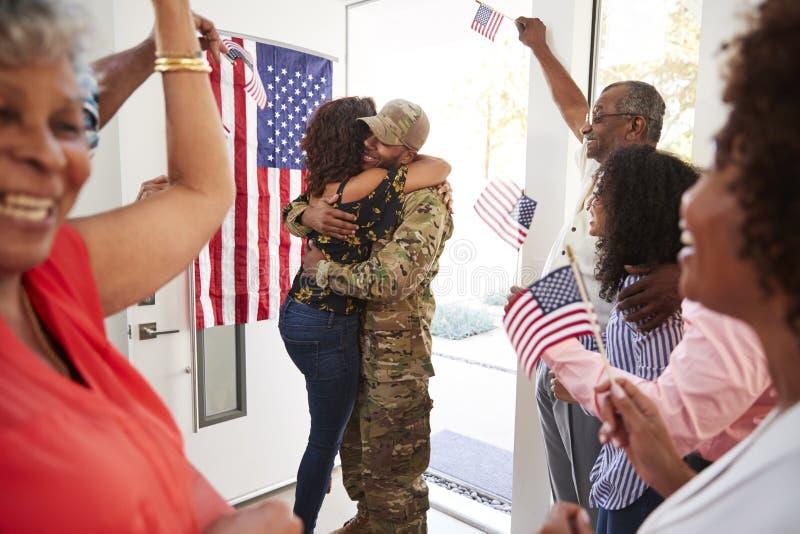 Millennial kobieta i rodzinnego powitalnego młodego amerykanin afrykańskiego pochodzenia żołnierz męski dom, obejmuje w drzwi, za obraz royalty free