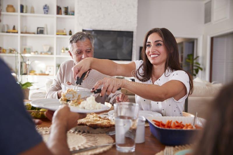 Millennial latinamerikansk kvinna som sitter på den tjänande som maten för tabell på ett familjmål, slut upp arkivfoton