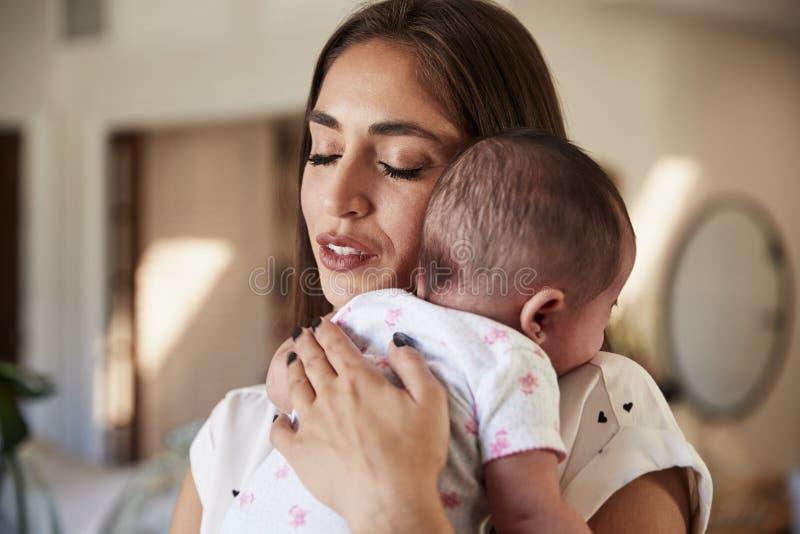 Millennial latynos matka z ona oczy zamykający, trzymający jej nowonarodzonego syna jej klatka piersiowa, zakończenie w górę zdjęcie stock