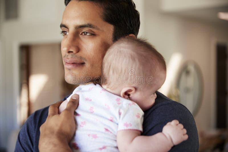 Millennial Latynoski ojciec trzyma jego nowonarodzonego syna blisko do jego klatki piersiowej, kierowniczego i ramion, zakończeni zdjęcie royalty free