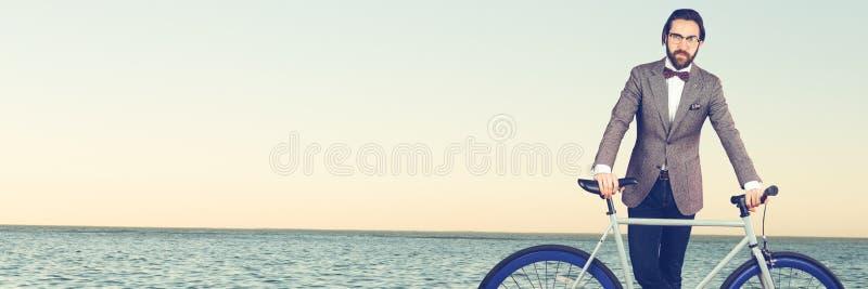 Millennial mężczyzna z łęku bicyklem przeciw horyzontowi i krawatem obrazy royalty free