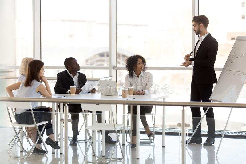 Millennial male mentor make flipchart presentation to colleagues royalty free stock photos