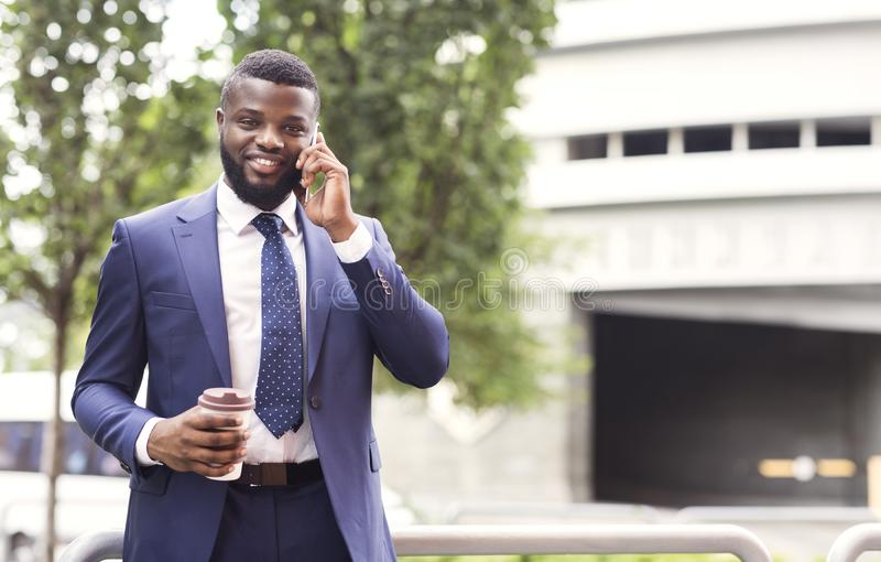 Millennial man in formal suit drinking coffee and using cellphone stock images