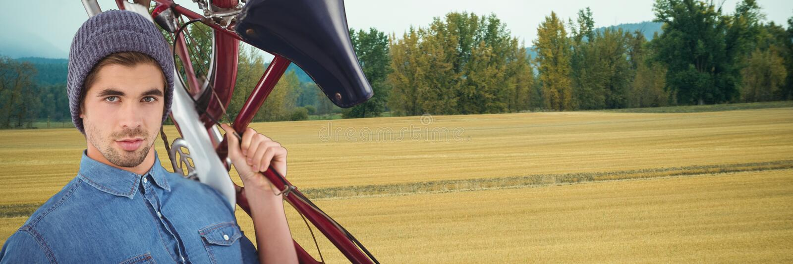 Millennial man holding bicycle against field stock photo