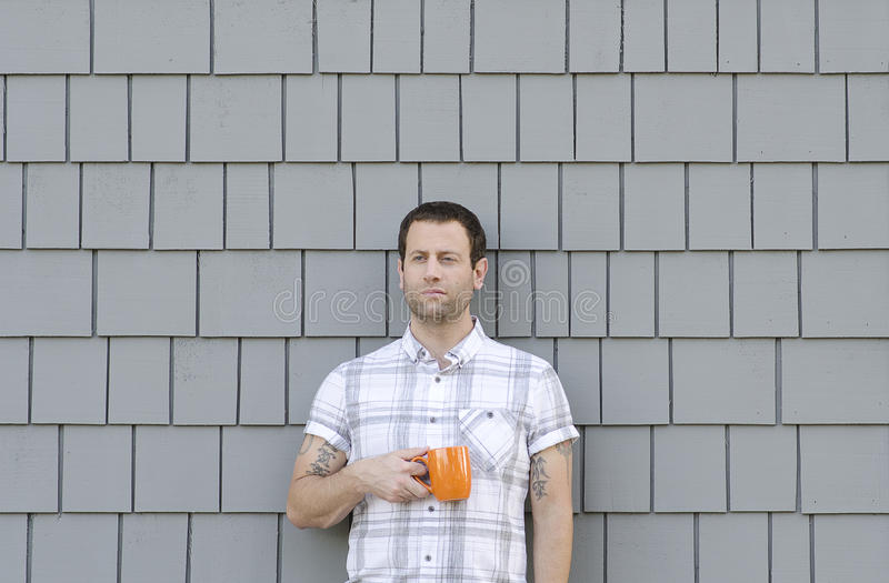 Millennial man holding a coffee mug with a grey neutral background. Millennial man in a white and gray plaid shirt holding an orange coffee mug with a grey royalty free stock images