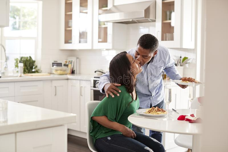 Millennial man kissing his partner as he serves a meal to her at their kitchen table, selective focus stock images