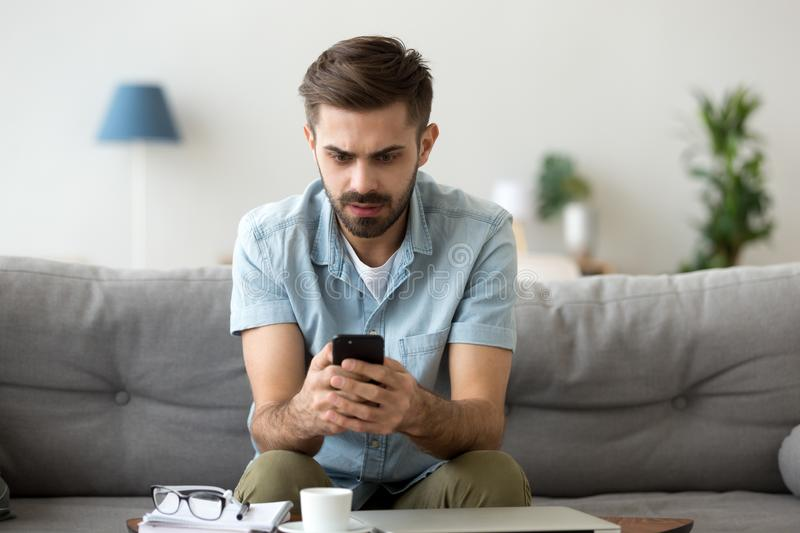 Confused man sit on couch shocked using smartphone stock photo