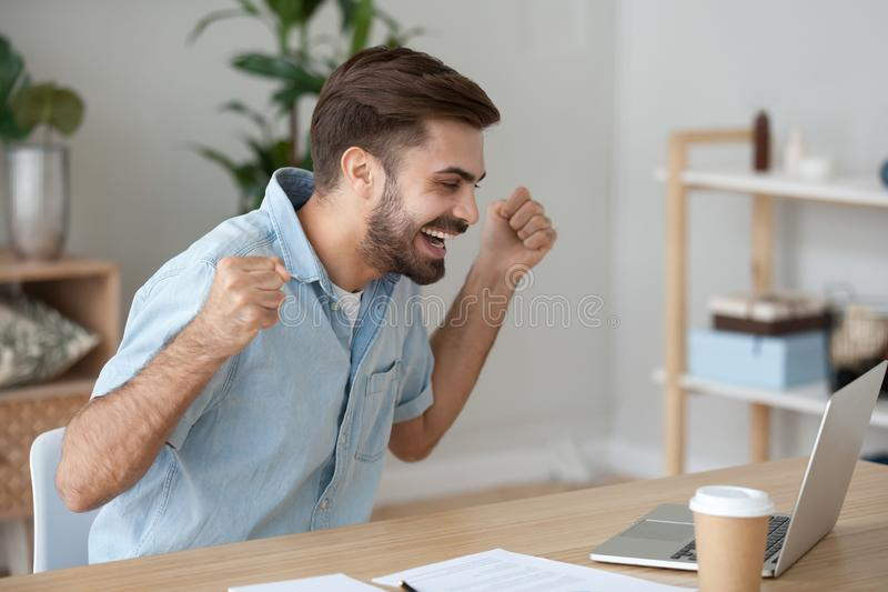 Excited happy man sitting at the desk looking at laptop. Millennial man sitting at the desk looking at computer device screen celebrating win feels happy stock images