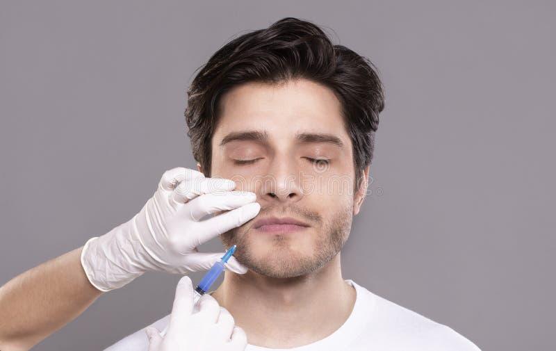 Millennial mens die hyaluronic collageeninjectie in kliniek krijgen royalty-vrije stock foto