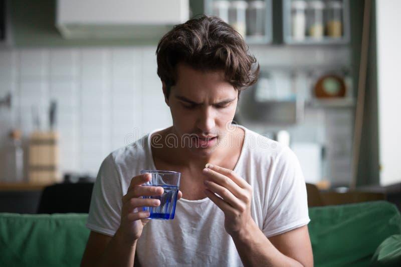 Millennial mens die pil nemen om thuis pijn te verlichten stock fotografie
