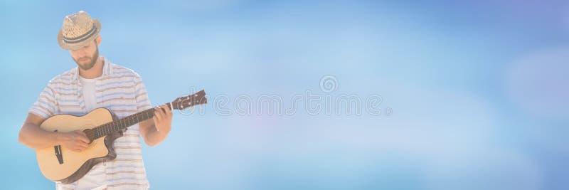 Millennial mens het spelen gitaar tegen onscherpe blauwe achtergrond stock foto