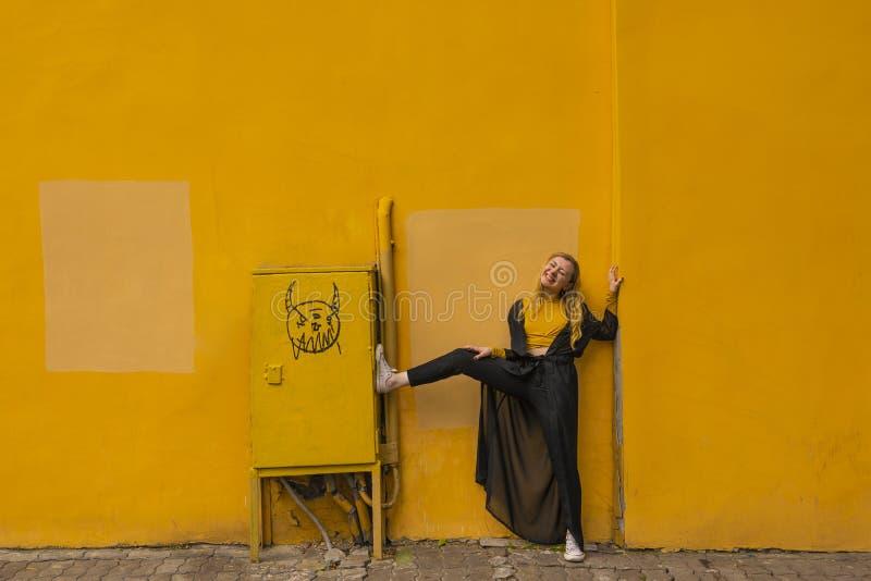 Millennial modieuze jonge blonde portret van het maniermeisje op een gele stadsachtergrond dichtbij de muur royalty-vrije stock afbeelding