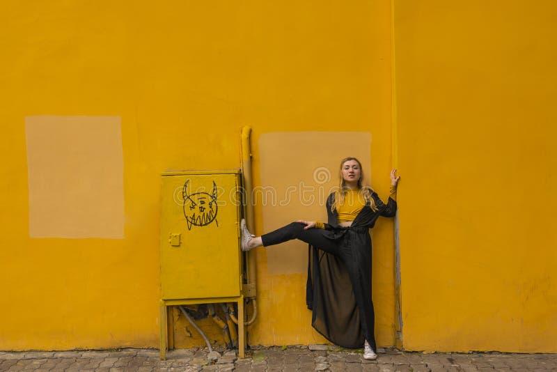 Millennial modieuze jonge blonde portret van het maniermeisje op een gele stadsachtergrond dichtbij de muur stock foto's