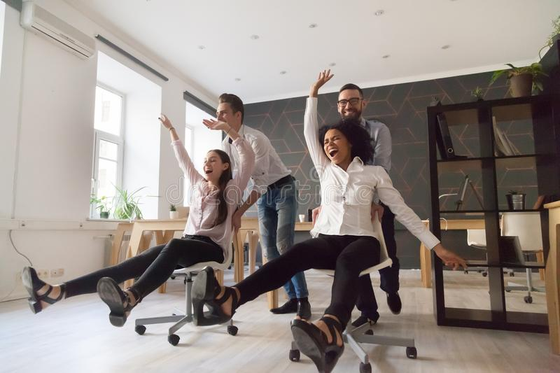 Millennial multiracial people having funny ride on chairs in off stock photo