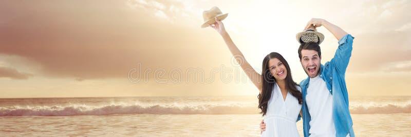 Millennial paar die met hoeden op zonsondergangstrand vieren stock afbeeldingen