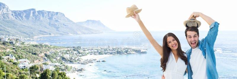 Millennial paar met hoeden tegen onscherpe kustlijn royalty-vrije stock foto