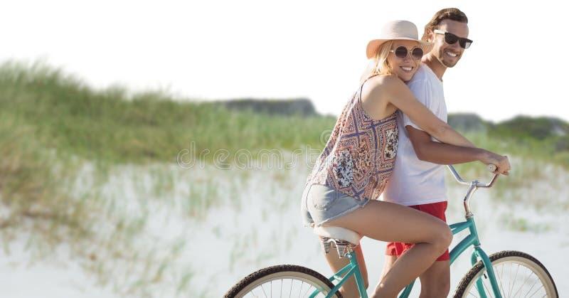 Millennial paar op fiets tegen zandduin royalty-vrije stock foto's