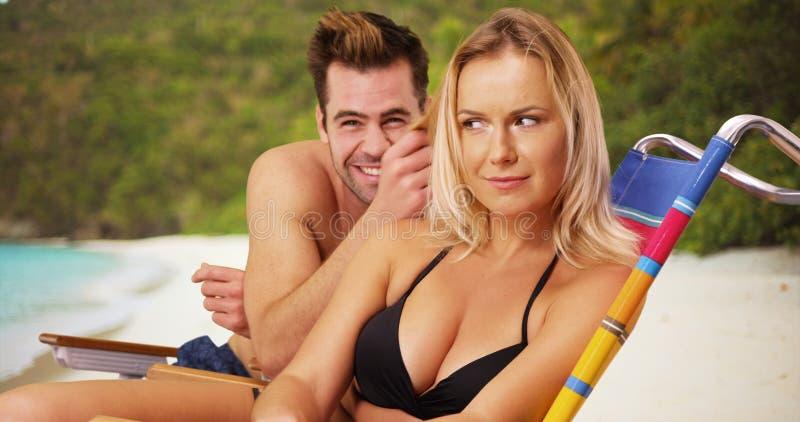 Millennial paarzitting samen bij het strand die het dwaze glimlachen bij camera zijn royalty-vrije stock afbeeldingen