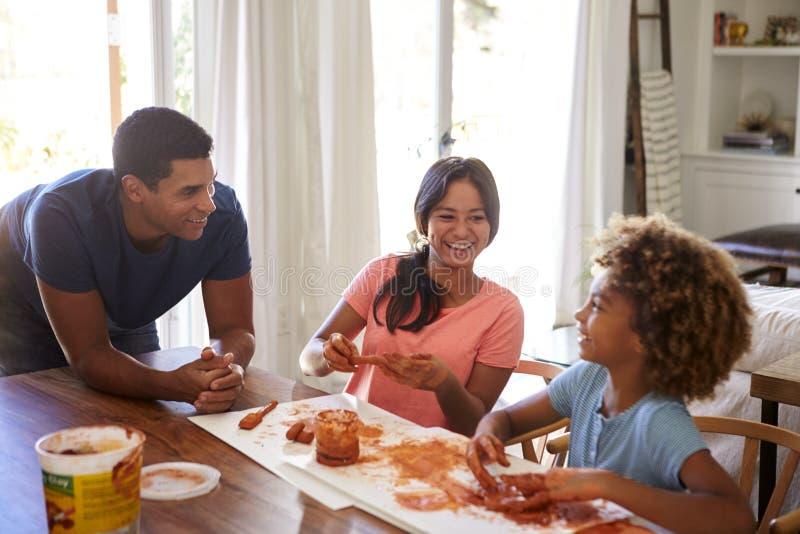 Millennial papa die op lijst leunen die op zijn dochter en haar meisje letten die met modelleringsklei spelen in de eetkamer stock fotografie