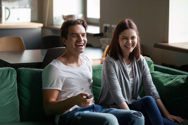 Millennial par som skrattar hållande ögonen på hållande fjärrkontroll för tv på royaltyfri foto