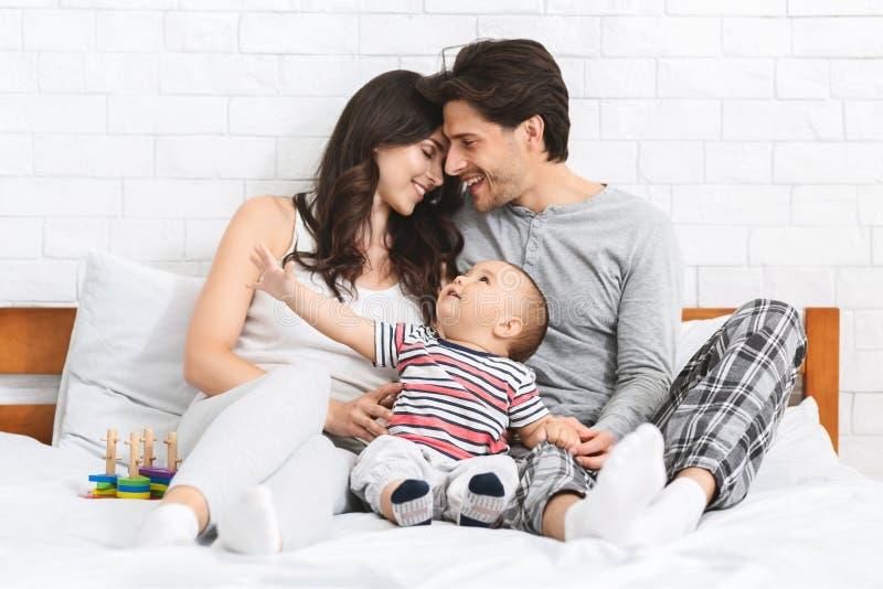 Millennial para w miłości obejmuje na łóżku z ciekawym dzieckiem zdjęcie royalty free