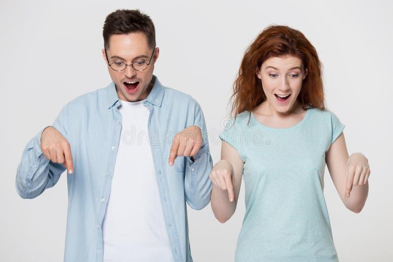 Millennial positieve paar voelt verbaasd richtend vingers onderaan studiobeeld stock foto