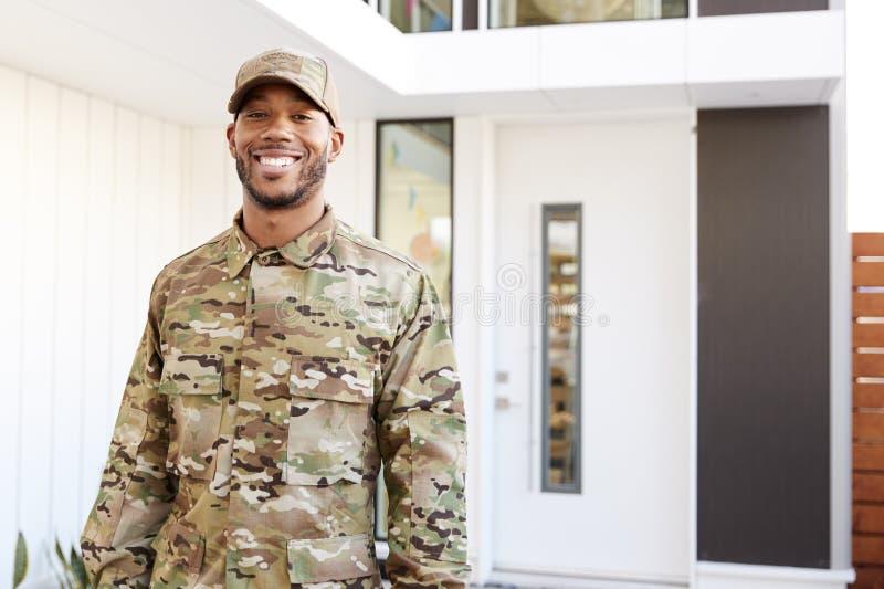 Millennial soldat i enhetligt anseende för kamouflage utanför modernt hus som ler till kameran, slut upp arkivfoto